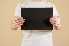 Mężczyzna trzyma czarnego A4 papier horizontally Ulotki prezentacja P Zdjęcie Royalty Free