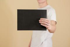 Mężczyzna trzyma czarnego A4 papier horizontally Ulotki prezentacja P Obraz Stock