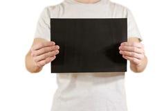 Mężczyzna trzyma czarnego A4 papier horizontally Ulotki prezentacja P Fotografia Stock