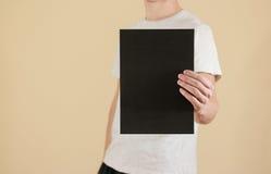 Mężczyzna trzyma czarnego A4 papier pionowo Ulotki prezentacja pam Zdjęcia Stock
