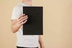 Mężczyzna trzyma czarnego A4 papier pionowo Ulotki prezentacja pam Zdjęcie Stock