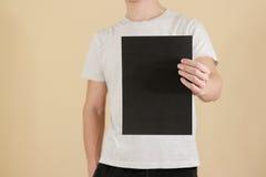 Mężczyzna trzyma czarnego A4 papier pionowo Ulotki prezentacja pam Fotografia Royalty Free
