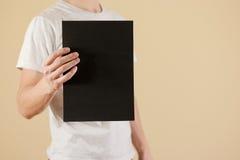 Mężczyzna trzyma czarnego A4 papier pionowo Ulotki prezentacja pam Zdjęcia Royalty Free