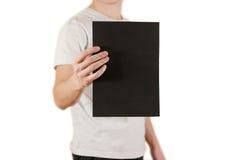 Mężczyzna trzyma czarnego A4 papier pionowo Ulotki prezentacja pam Fotografia Stock