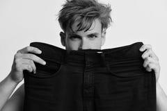 Mężczyzna trzyma czarnych cajgi ampuła rozmiar Ciężar strata i mody pojęcie Atleta z upaćkanym włosy obrazy stock