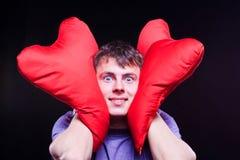 Mężczyzna trzyma dwa czerwonego serca kształtnej poduszki Zdjęcia Royalty Free