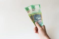 Mężczyzna trzyma dwieście dolarów australijskich notatek w jego ręka Fotografia Royalty Free