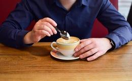Mężczyzna trzyma filiżankę cappuccino zdjęcie royalty free