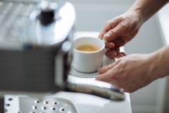 Mężczyzna trzyma filiżankę kawa espresso obok kawowego producenta Zdjęcia Stock