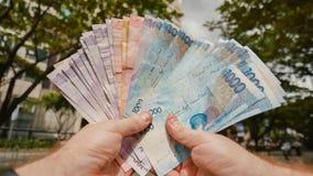 Mężczyzna trzyma Filipińskich pieniędzy rachunki w jego rękach zdjęcia stock