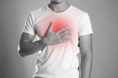 Mężczyzna trzyma jego klatki piersiowej klatki piersiowej ból bastiony Hearth zdjęcie royalty free