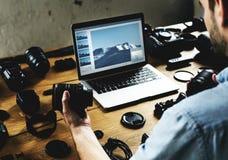 Mężczyzna trzyma kamera obiektyw zapowiedzi fotografię na laptopie i Fotografia Stock