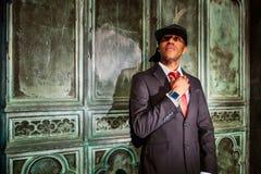 Mężczyzna trzyma krawat w kostium pozyci przed starymi drzwiami Zdjęcie Royalty Free