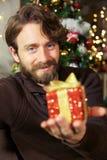 Mężczyzna trzyma mały czerwieni pudełka bożych narodzeń teraźniejszości ono uśmiecha się Obrazy Royalty Free