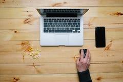 Mężczyzna trzyma pigułkę Drewniany countertop, laptop Zdjęcia Royalty Free