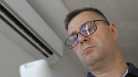 Mężczyzna trzyma pilota do tv i obraca dalej powietrze uwarunkowywać w domu z szkłami Rozszczepiony system dołączający zbiory