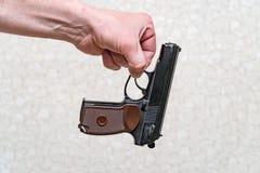 Mężczyzna trzyma pistolet z dwa palcami na szarym tle obrazy stock