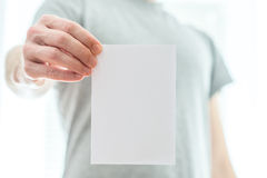 Mężczyzna trzyma pustego białego kawałek papieru w popielatej koszulce Zdjęcia Royalty Free