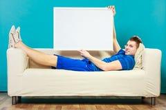 Mężczyzna trzyma pustej prezentaci deskę na kanapie Obraz Stock