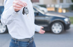Mężczyzna trzyma samochodowego klucz obok pojazdu Fotografia Royalty Free