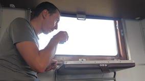 Mężczyzna trzyma smartphone i pije siedzi na taborowym Kolejowym frachcie kawę i herbaty zwolnionego tempa wideo zbiory wideo