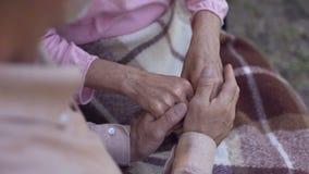 Mężczyzna trzyma stare kobiet ręki, rodzinną miłości i opieki, stara para w karmiącym domu zbiory