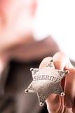 Mężczyzna trzyma szeryf odznakę Zdjęcia Stock