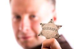Mężczyzna trzyma szeryf odznakę Zdjęcie Stock