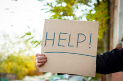 Mężczyzna trzyma szyldową saying pomoc Zdjęcia Royalty Free