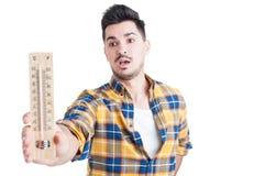 Mężczyzna trzyma termometr w jego ręce w koszula Fotografia Royalty Free
