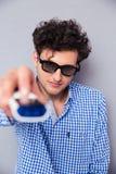 Mężczyzna trzyma TV daleki w 3d szkłach Fotografia Stock
