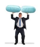 Mężczyzna trzyma up gigantyczne pigułki mówi opiekę zdrowotną Zdjęcia Royalty Free