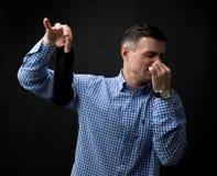 Mężczyzna trzyma zaśmierdłe skarpety i zatykającego nos Obrazy Stock
