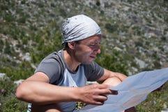 Mężczyzna turysta w górze czyta mapę Fotografia Stock