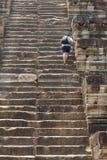 Mężczyzna turysta wspina się wysokiego schodek antyczna świątynia Niekończący się kroki antyczna buddyjska świątynia w Angkor Wat Zdjęcia Stock
