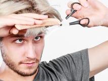 Mężczyzna tworzy nową fryzurę z nożycami i gręplą Fotografia Royalty Free