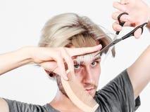 Mężczyzna tworzy nową fryzurę z nożycami i gręplą Zdjęcia Royalty Free