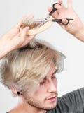 Mężczyzna tworzy nową fryzurę z nożycami i gręplą Obraz Royalty Free