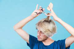 Mężczyzna tworzy nową fryzurę z nożycami i gręplą Obrazy Royalty Free