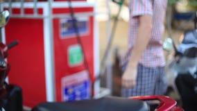Mężczyzna używa benzynowej pompy nozzle benzyny podsadzkowego paliwo zbiornik motocykl w olej stacji Tajlandia 1920x1080 zbiory
