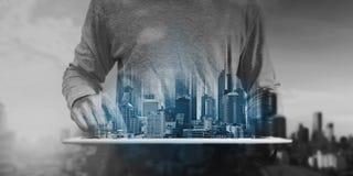 Mężczyzna używa cyfrową pastylkę i nowożytny budynku hologram, Nieruchomość biznes i budynek technologii pojęcie zdjęcie stock
