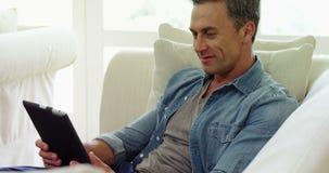 Mężczyzna używa cyfrową pastylkę w żywym pokoju zdjęcie wideo