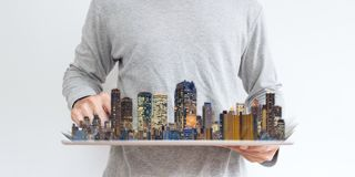 Mężczyzna używa cyfrową pastylkę z nowożytnym budynku hologramem Nieruchomość biznes i inwestycja, budynek technologia fotografia stock