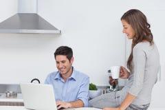 Mężczyzna używa jego laptop w kuchni Zdjęcia Royalty Free