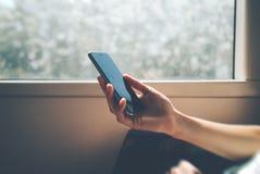 Mężczyzna używa jego smartphone zakończenie okno Obrazy Royalty Free