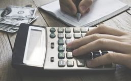 Mężczyzna używa kalkulatora pisze w notatniku liczenie robi notatkom przy biurową ręką jest obraz royalty free