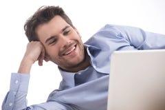 Mężczyzna używa komputer. Rozochoceni młodzi człowiecy używa komputer podczas gdy isol Obrazy Royalty Free