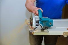 mężczyzna używa kurendę zobaczył dla tnącej drewnianej drzwiowej budowy i domowego odświeżania, naprawy narzędzie zdjęcie royalty free