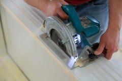 mężczyzna używa kurendę zobaczył dla tnącej drewnianej drzwiowej budowy i domowego odświeżania, naprawy narzędzie obraz stock