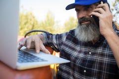 Mężczyzna używa laptop podczas gdy opowiadający na telefonie komórkowym zdjęcie stock